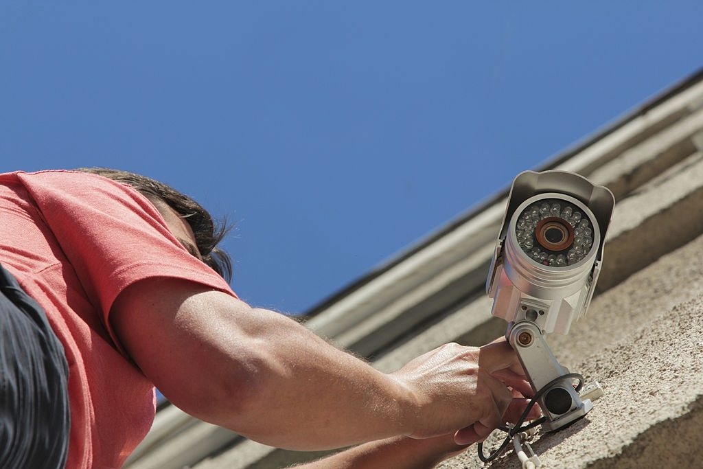 Electrical Worker splicing wires on security camera